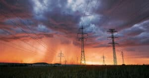 Photo of electricity towers under cloudy skies.