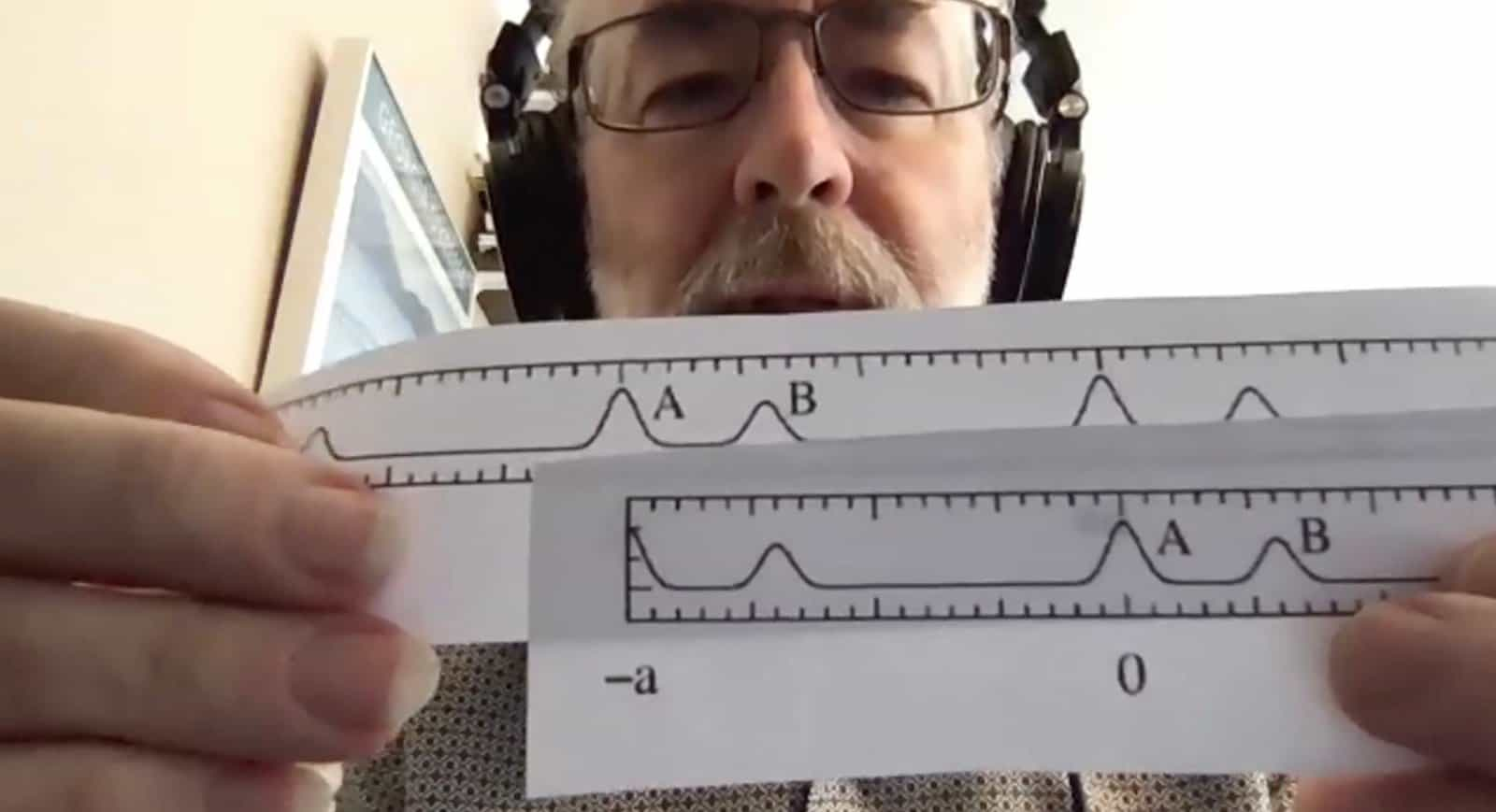 Professor Brent Fultz holding up paper with data to computer camera on a virtual call.