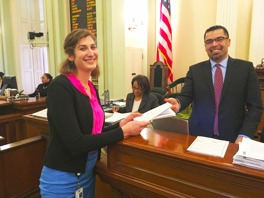 Photo of Jen Chase, PhD, a 2017 CCST Science & Technology Policy Fellow, handing a bill across the desk on the floor of the California State Assembly.