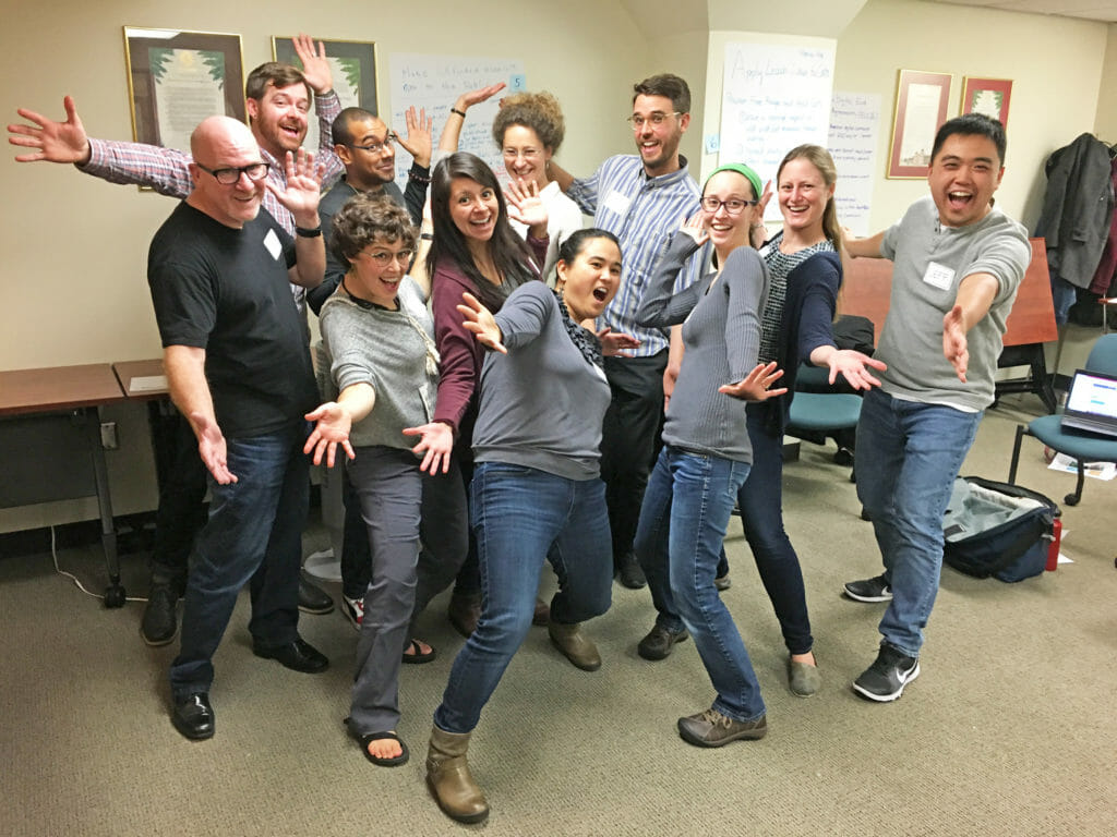 "The 2018 CCST Science & Technology Policy Fellows during their ""policy boot camp"" training month in November 2017, with improv instructor Steve Pierce. Everyone is smiling with ""jazz hands"" and arms wide open."
