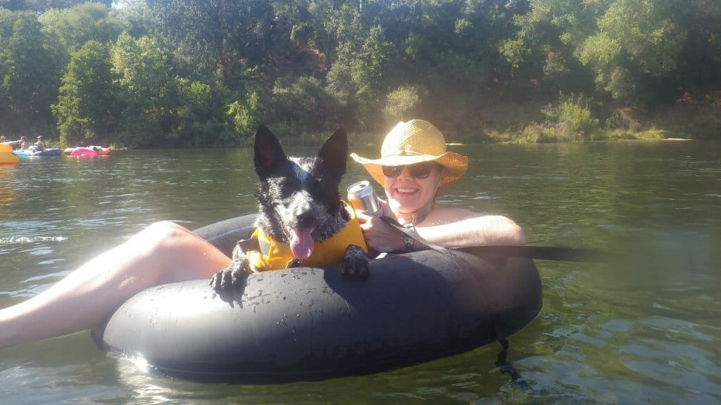 Photo of Angee Doerr, wearing a straw hat and sitting in an inner tube with a dog, while floating on the American River in Sacramento.