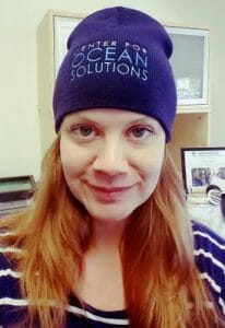 Portrait photo of Angee Doerr, PhD, Commander in the U.S. Navy Reserve. Angee is wearing a blue knit cap with the Center for Ocean Solutions logo.