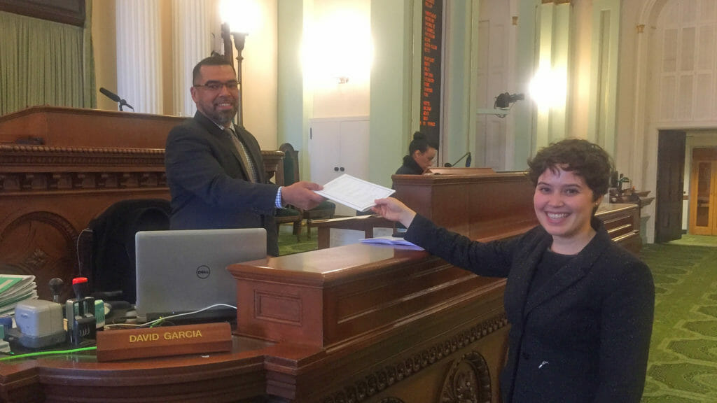 Gilson giving bill across desk