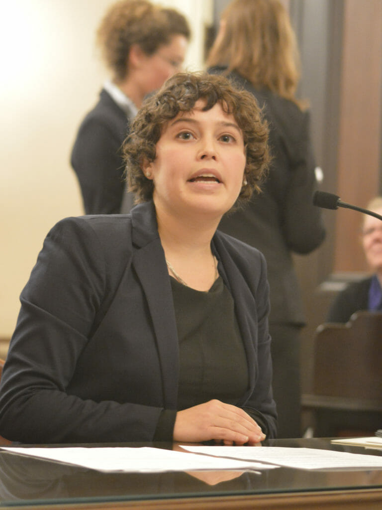 """2018 CCST Science Fellow Amy Gilson presents a bill during the annual mock hearing exercise held as part of the """"policy boot camp"""" for incoming fellows. Amy is wearing a gray suit and sitting before a microphone in a State Senate hearing room."""