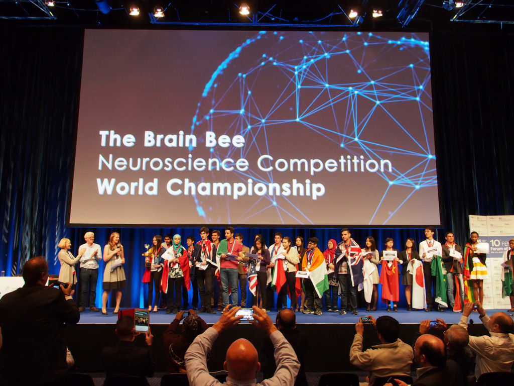 "Julianne McCall on a large theatre stage surrounded by students. Julianne McCall presenting at ""The Brain Bee"" Neuroscience Competition World Championship. (Image courtesy of Julianne McCall)"