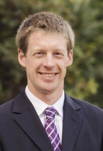 Portrait photo of Mike Peterson, PhD, a 2017 CCST Science & Technology Policy Fellow. Mike is wearing a plaid purple tie and a navy jacket, standing in front of landscaping at the State Capitol.
