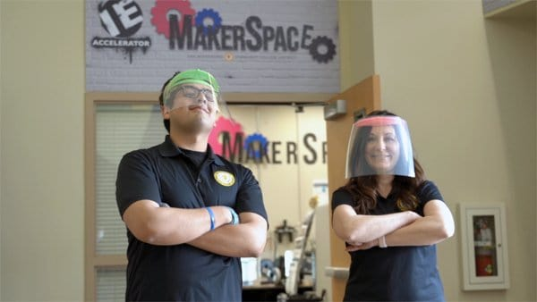 Two makers wearing medical-grade face shields created using their 3D printer technology.