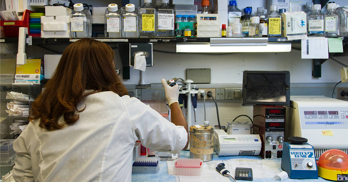 Photo of a scientist at a lab bench conducting an experiment.
